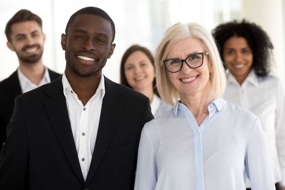 A photograph of a diverse old and young group of employees