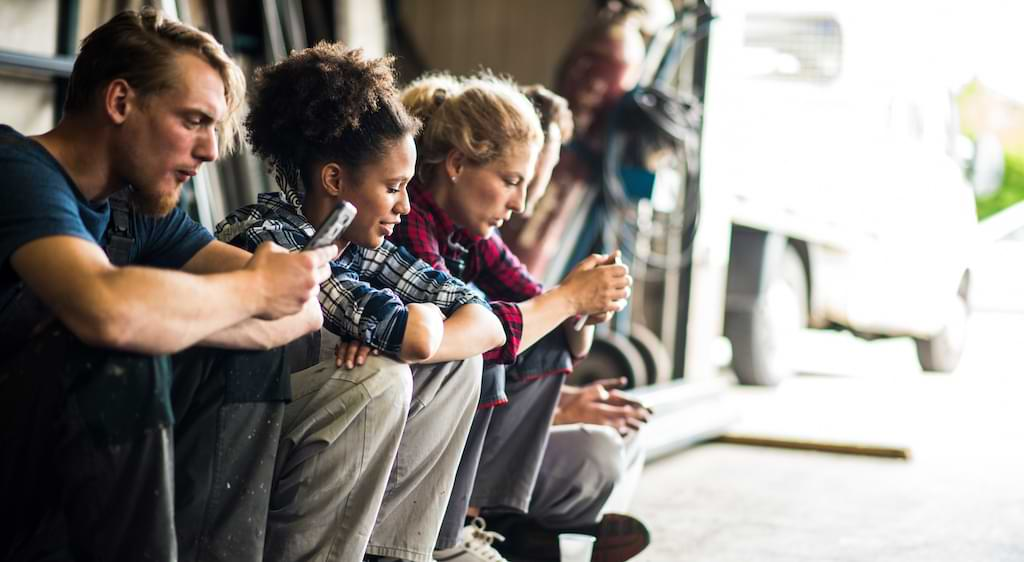 An illustration of young workers glued to their smartphones.