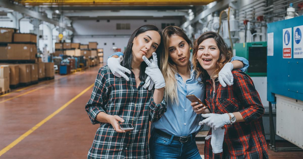 Junge Mitarbeiterinnen mit Smartphone in der Werkshalle