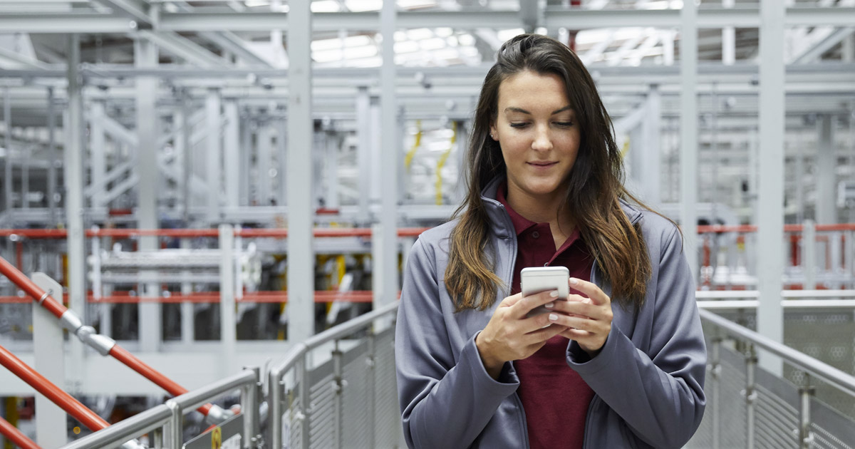 A picture of a Young Woman Factory Worker with her Smartphone.